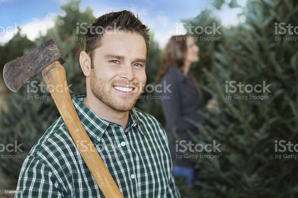 Man with axe selecting Christmas tree to cut down royalty-free stock photo