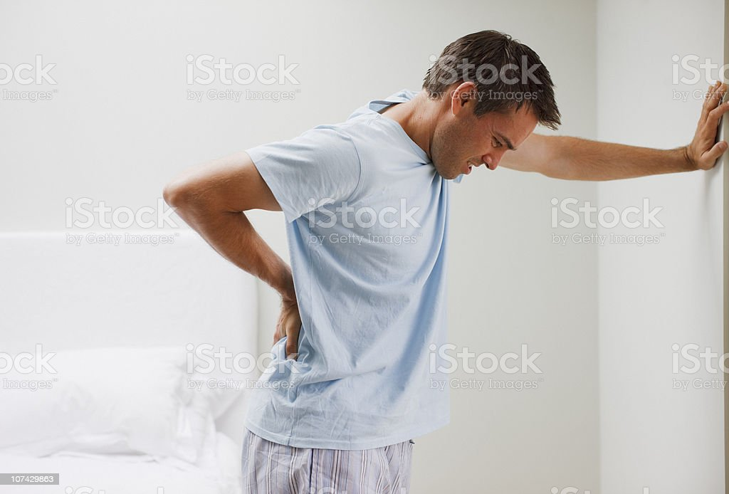 Man with backache leaning against wall stock photo