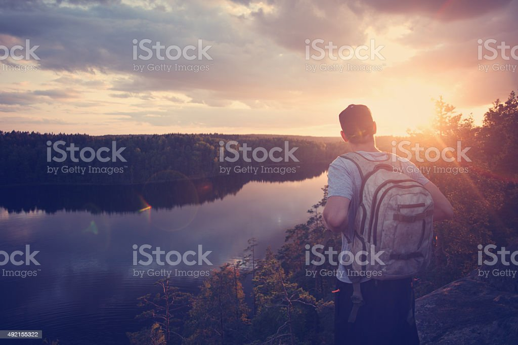 Man with backpack looking at sunset near river stock photo