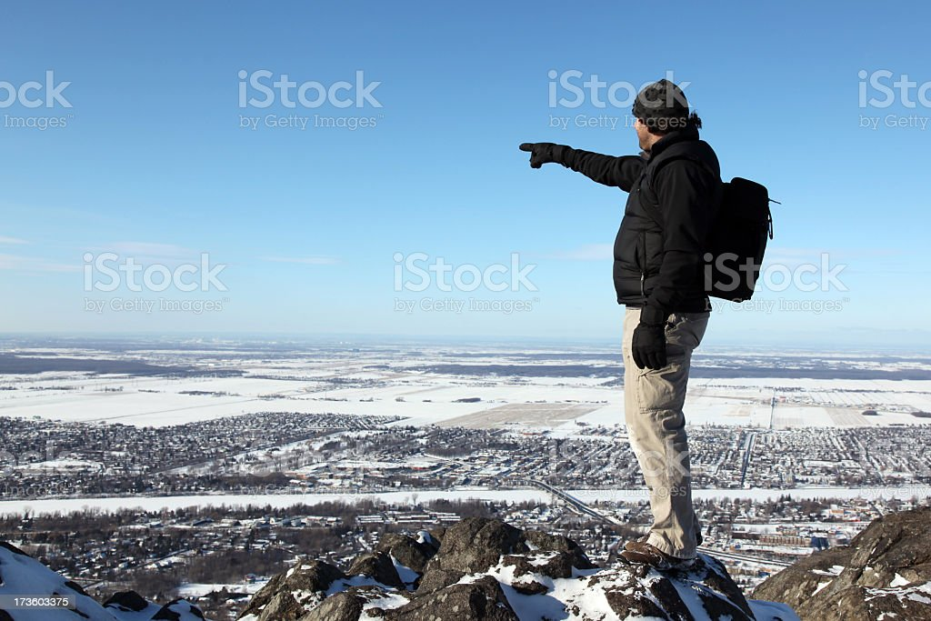 Man with Backpack on Mountain Summit Pointing a Direction stock photo