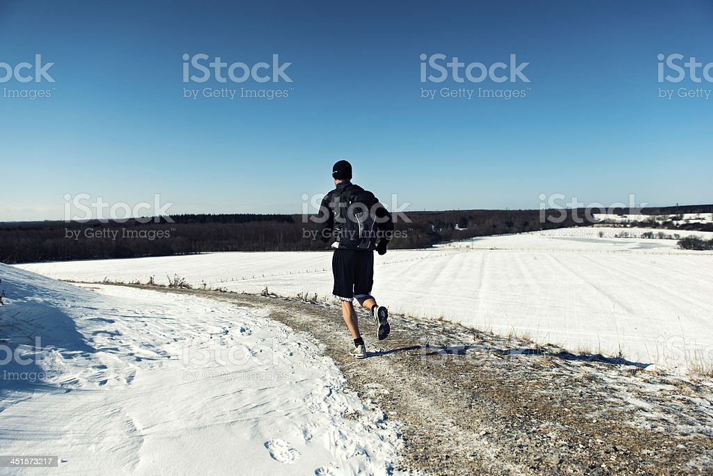 Man with backpack out for a run in the snow royalty-free stock photo