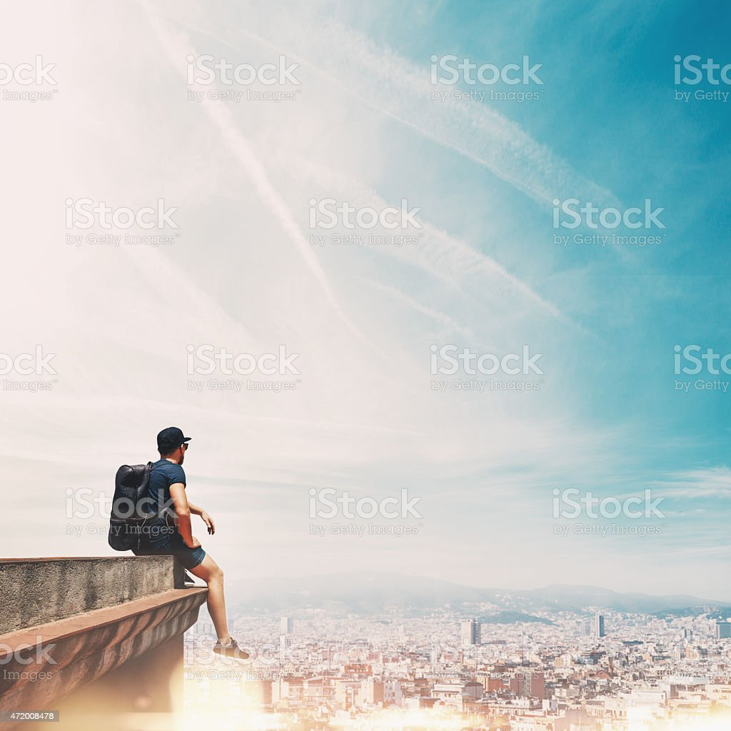 Man with backpack seated on top of a roof overlooking city stock photo