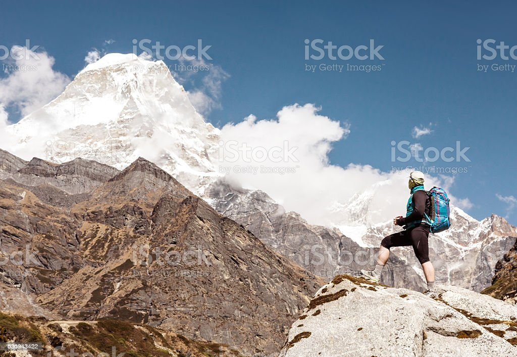 Man with Backpack staying on Rock in high Mountains stock photo