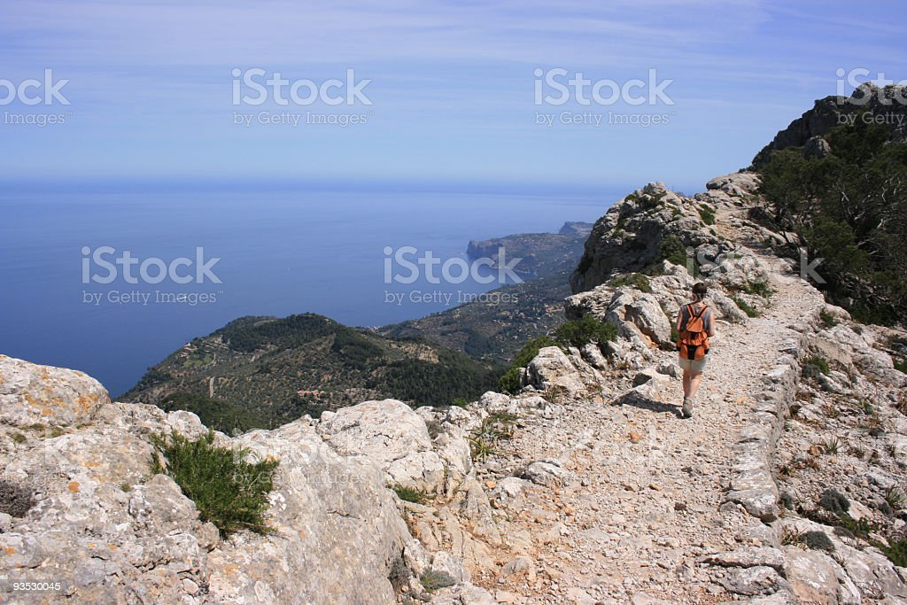 Man with backpack walking along rocky path in Tramuntana royalty-free stock photo