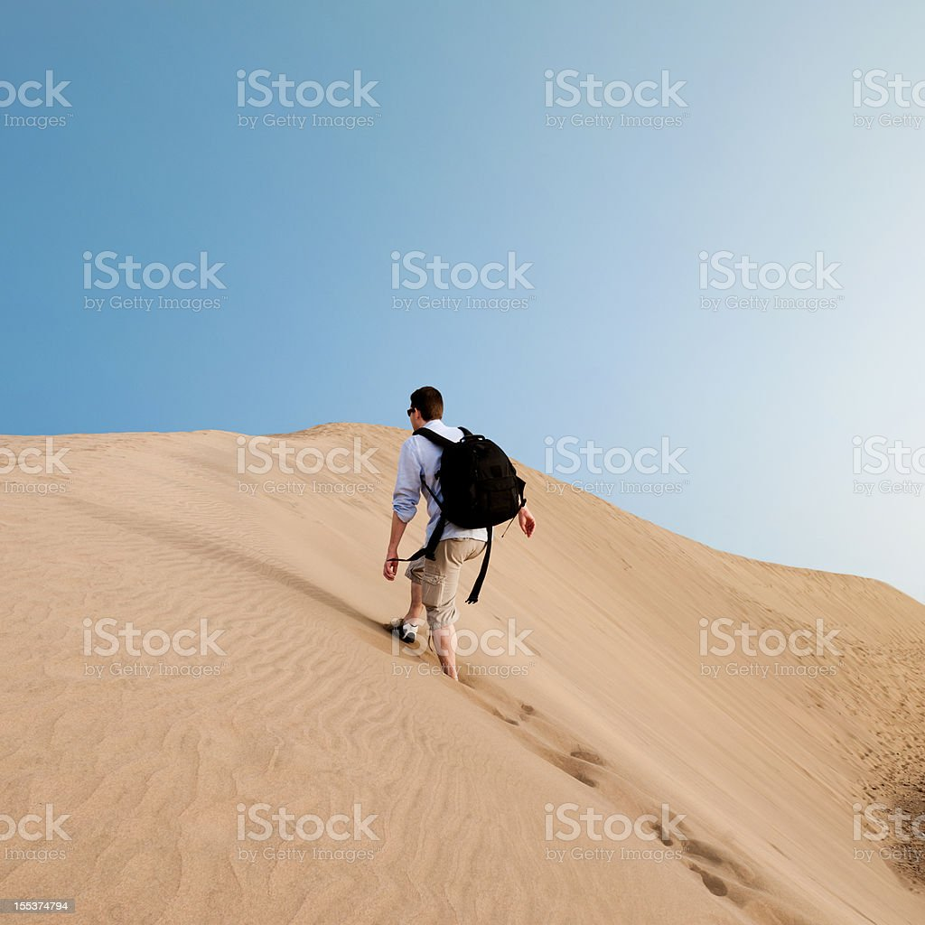 Man with backpack walks through the desert royalty-free stock photo