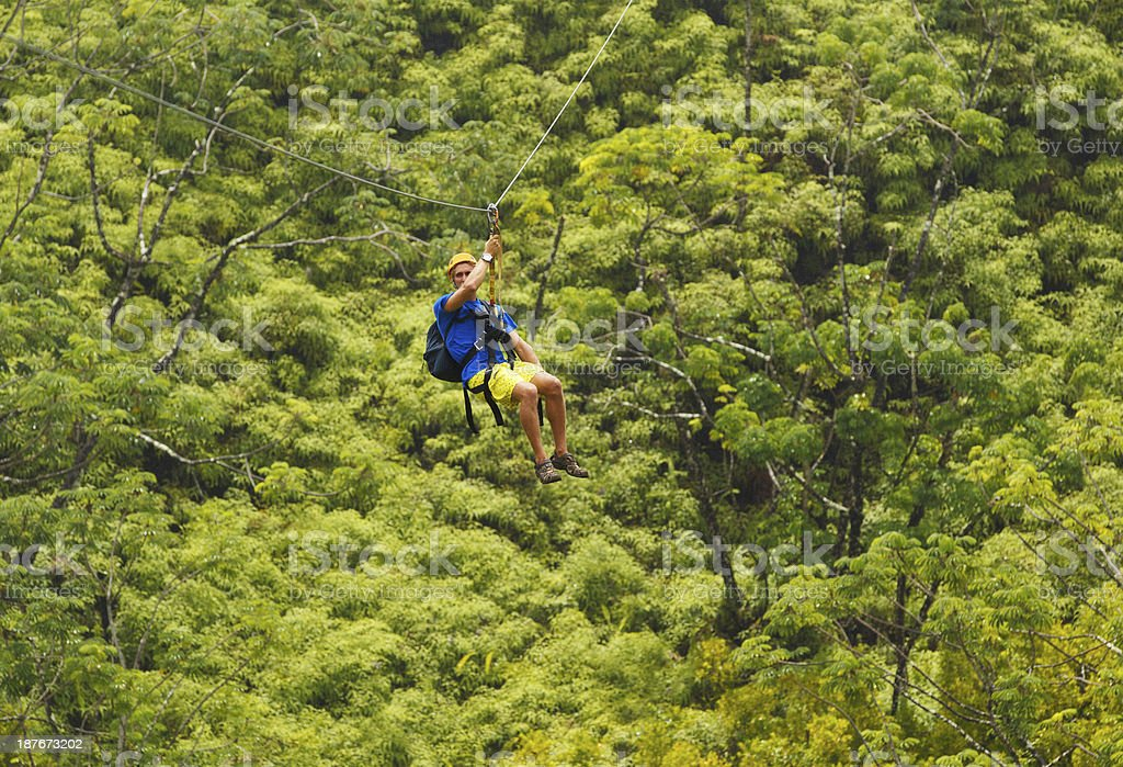 Man with backpack ziplining through a forest stock photo