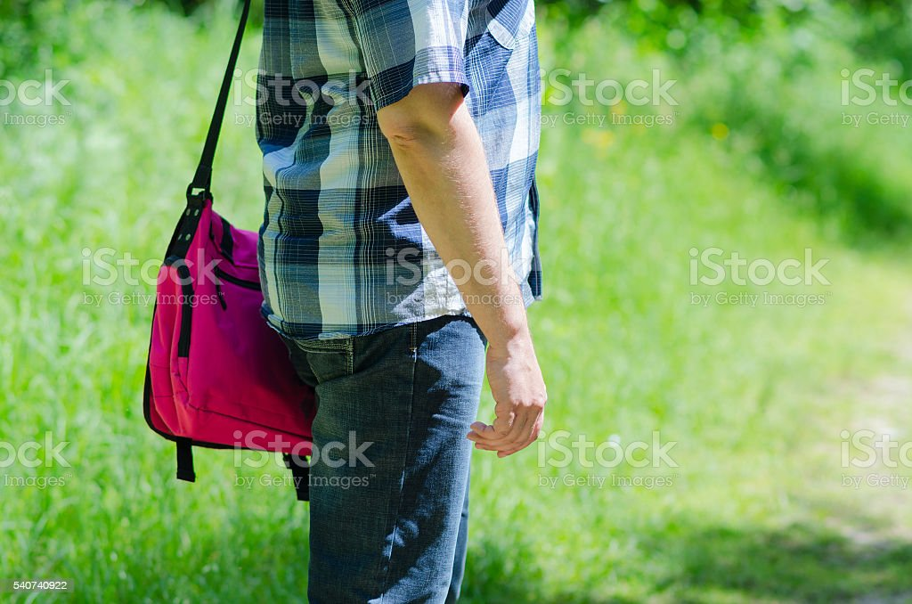 Man with bag for notebook on shoulder stands on path stock photo