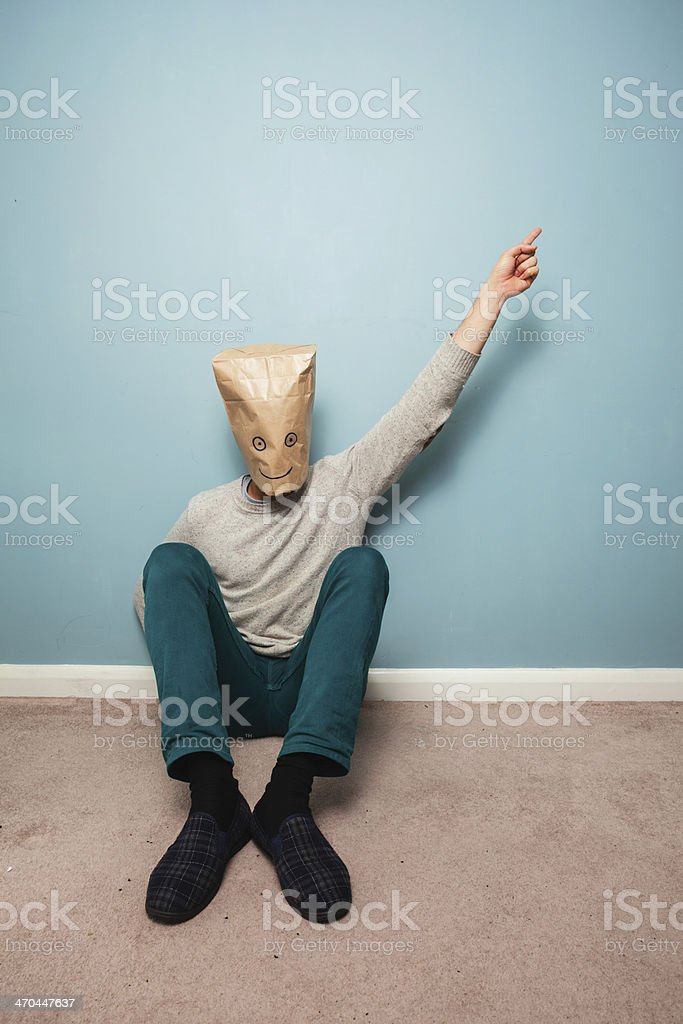 Man with bag over head on floor is pointing stock photo
