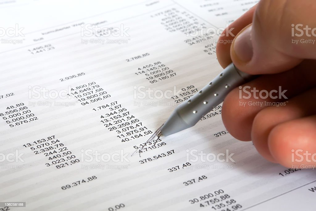 Man with balance spreadsheet and pen stock photo