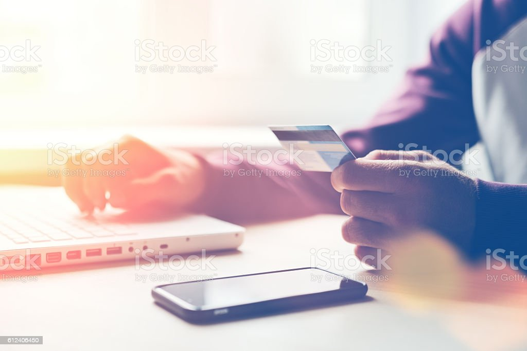 Man with bank card and laptop making online shopping stock photo