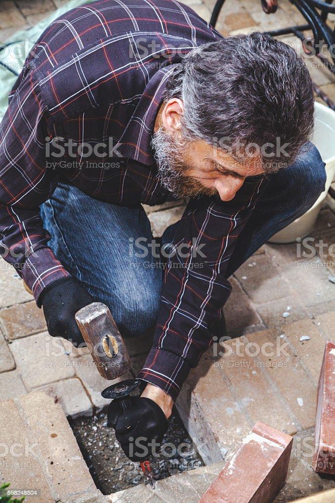man with beard breaks masonry hammer and chisel stock photo