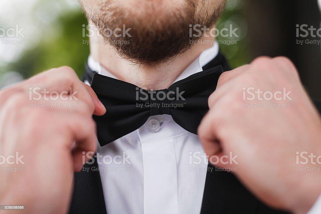 Man with beard correcting his bowtie stock photo