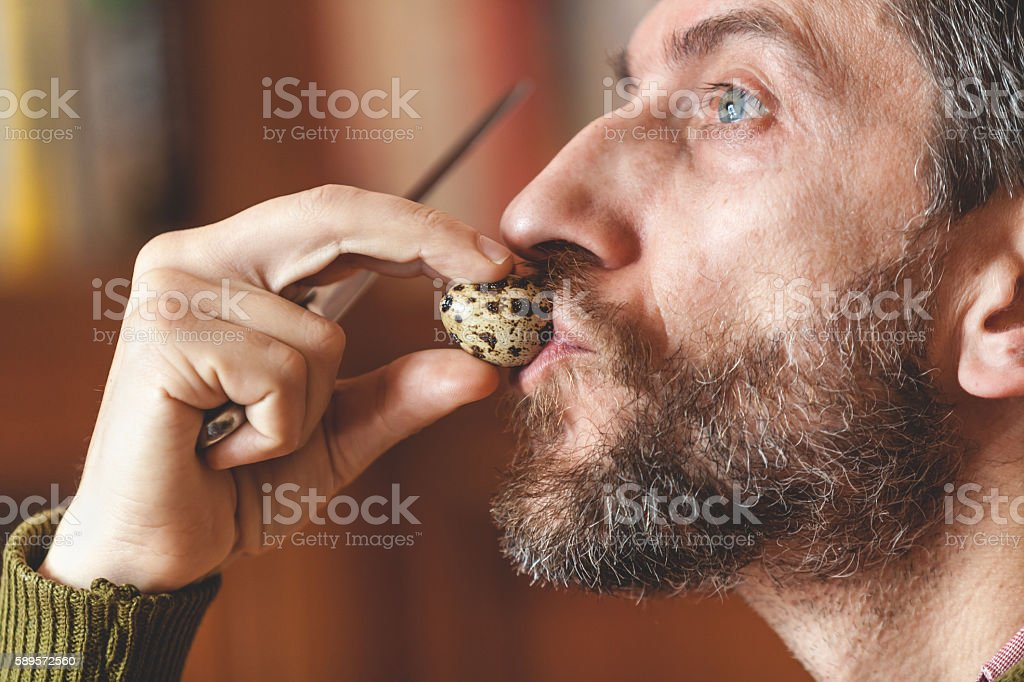 Man with beard drink quail egg stock photo