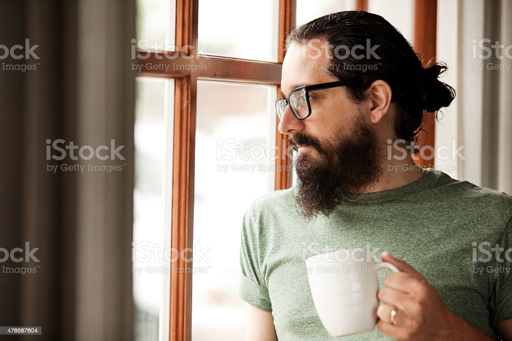 Man With Beard Holding Coffee Mug And Looking Out Window stock photo
