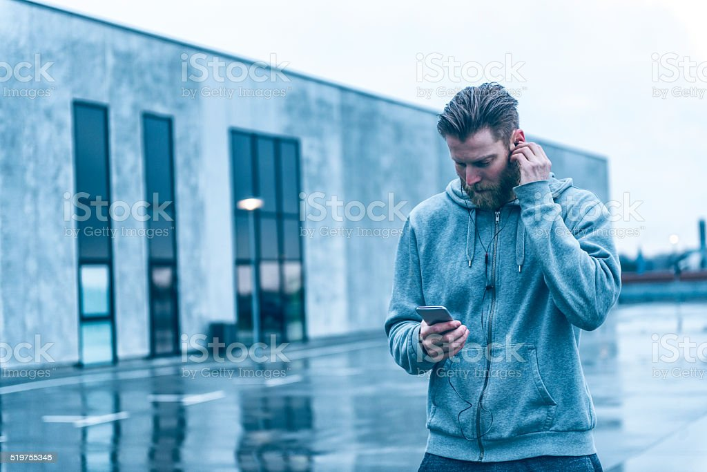 Man with beard listens to music on smart phone outside stock photo