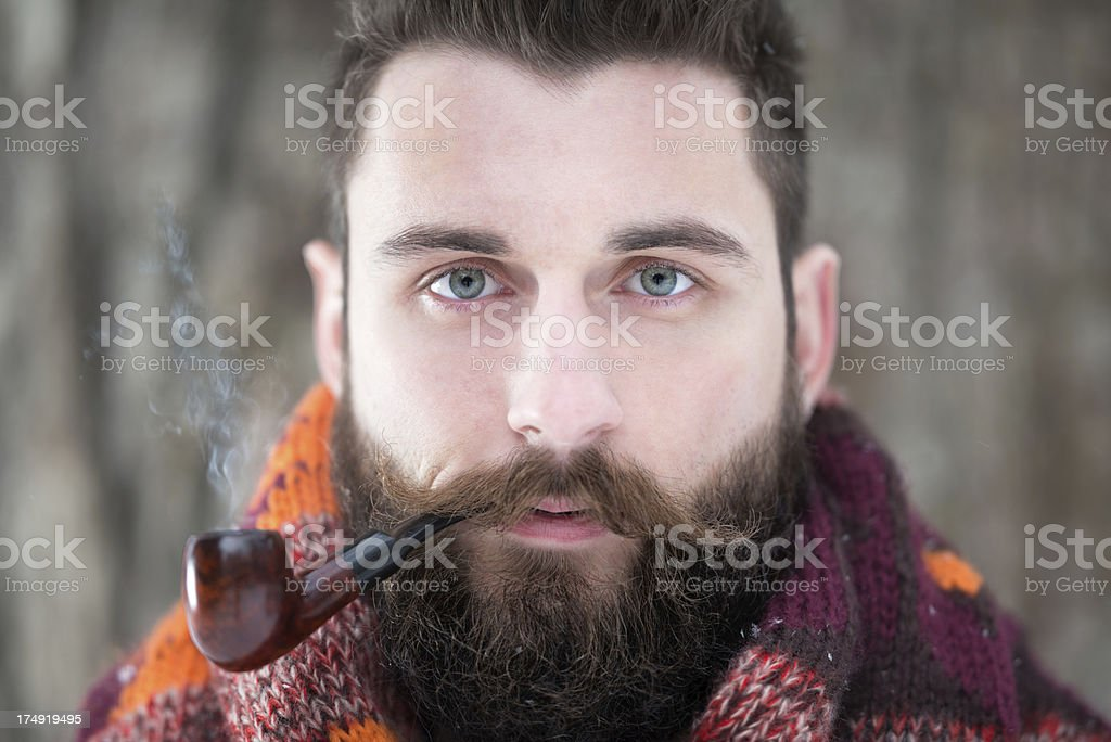 Man with Beard puffing away at his Pipe royalty-free stock photo