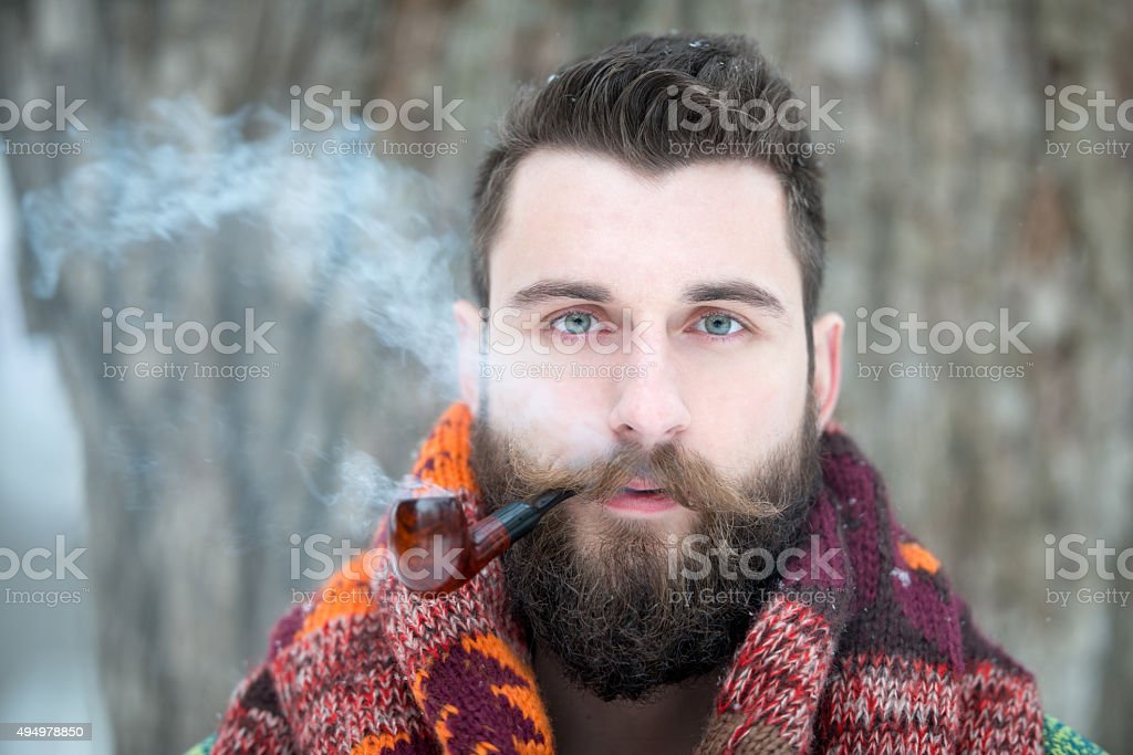 Man with Beard puffing away at his Pipe stock photo