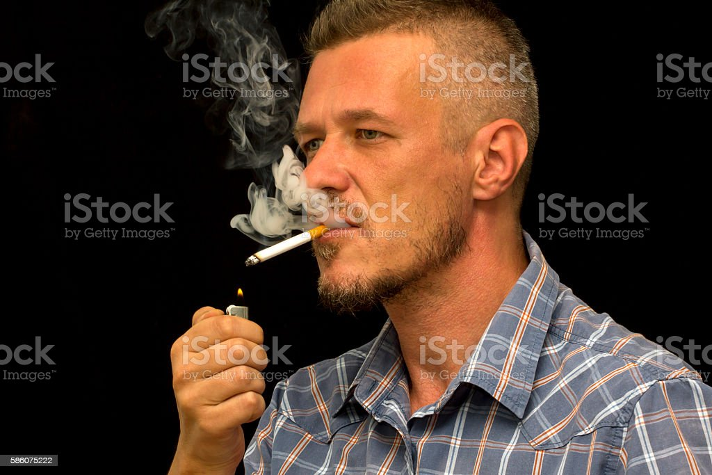Man with beard smoking cigarette in a dark room stock photo