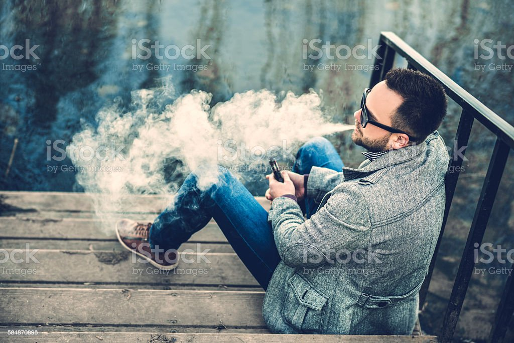 Man with beard vaping outdoor electronic sigarette stock photo