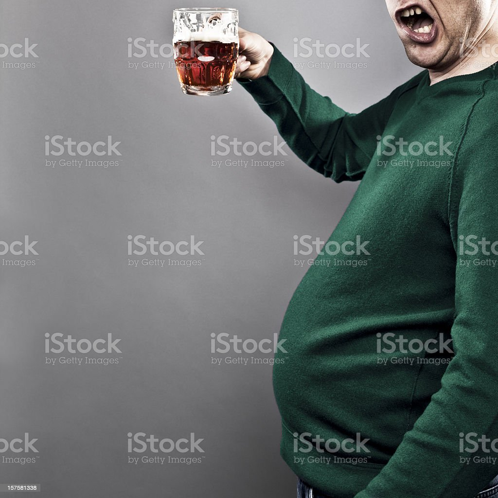 Man with beeer belly enjoying a pint stock photo