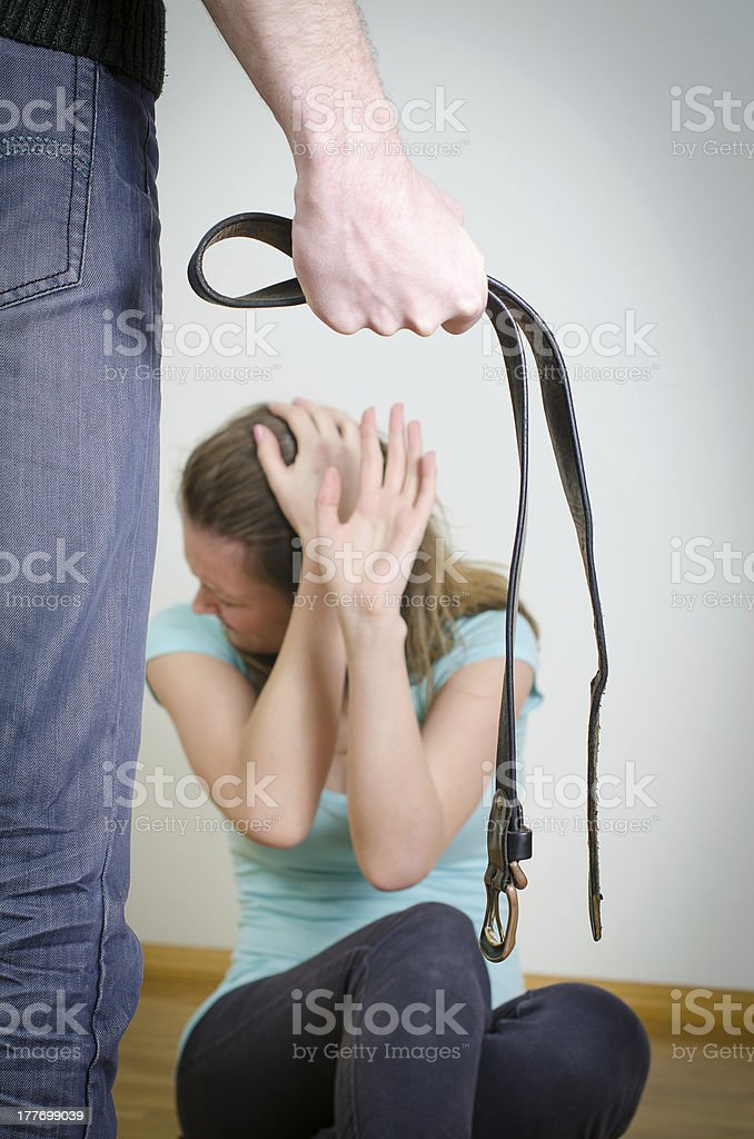 Man with belt coming to his wife. stock photo