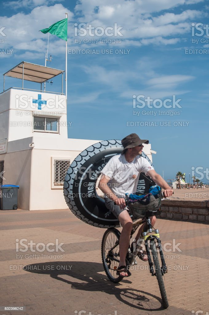 man with bicycle and buoy near  lifeguard station stock photo