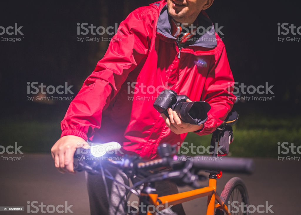 Man with bicycle holding a camera outdoors stock photo