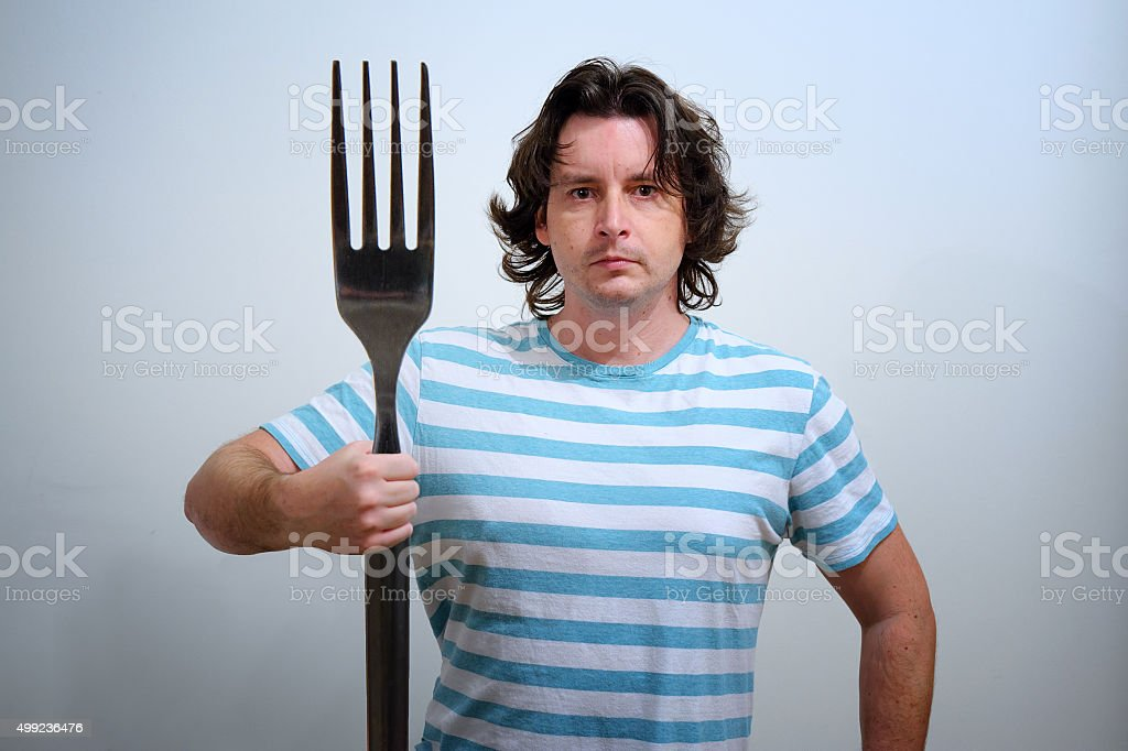 Man with big fork as a Neptune trident stock photo