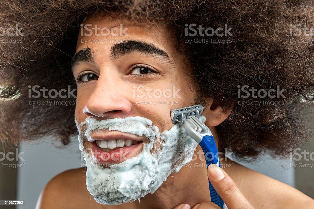 man with big hair shaving beard stock photo