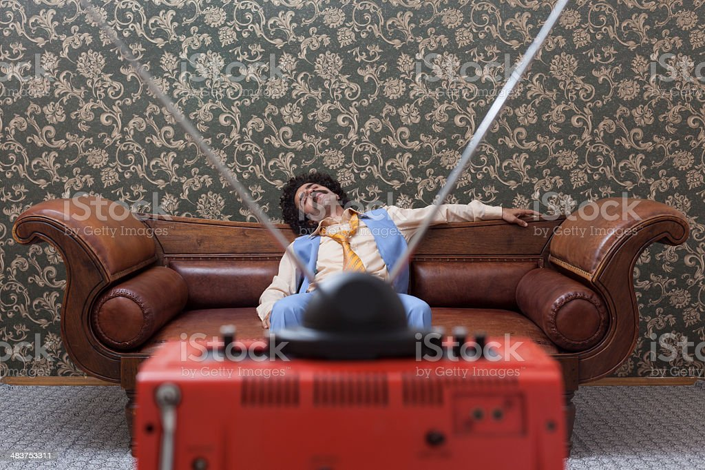 Man with big hair sleeping on couch while watching television royalty-free stock photo