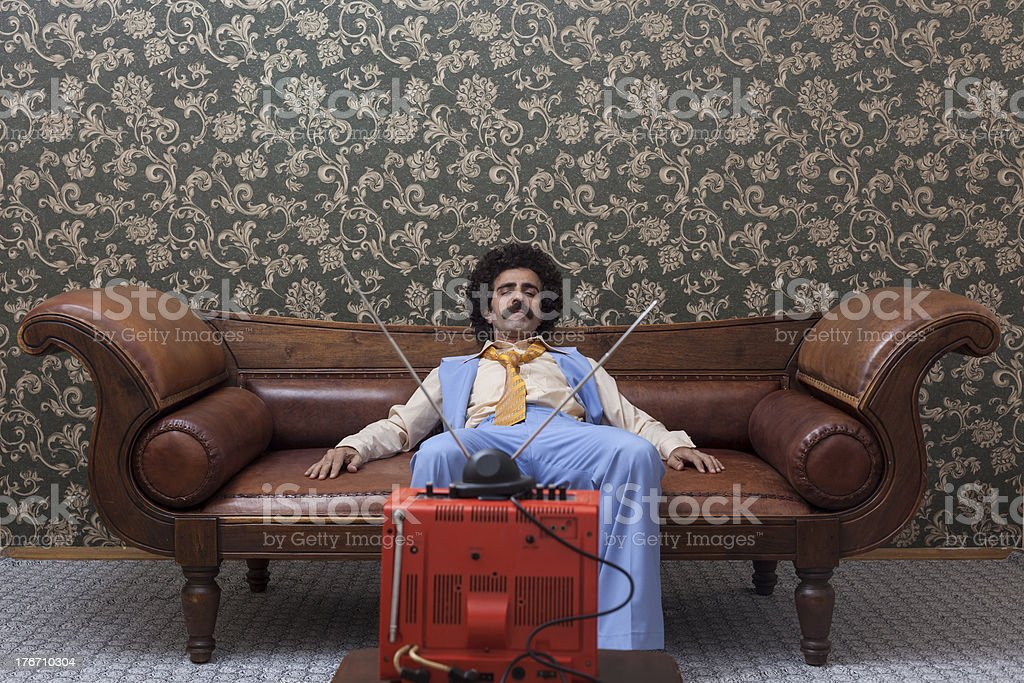 Man with big hair watching television royalty-free stock photo