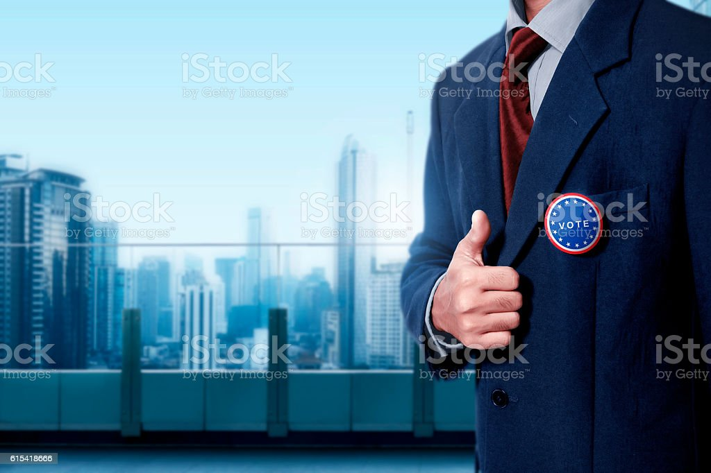 Man with black business suit with blue pinned button written stock photo