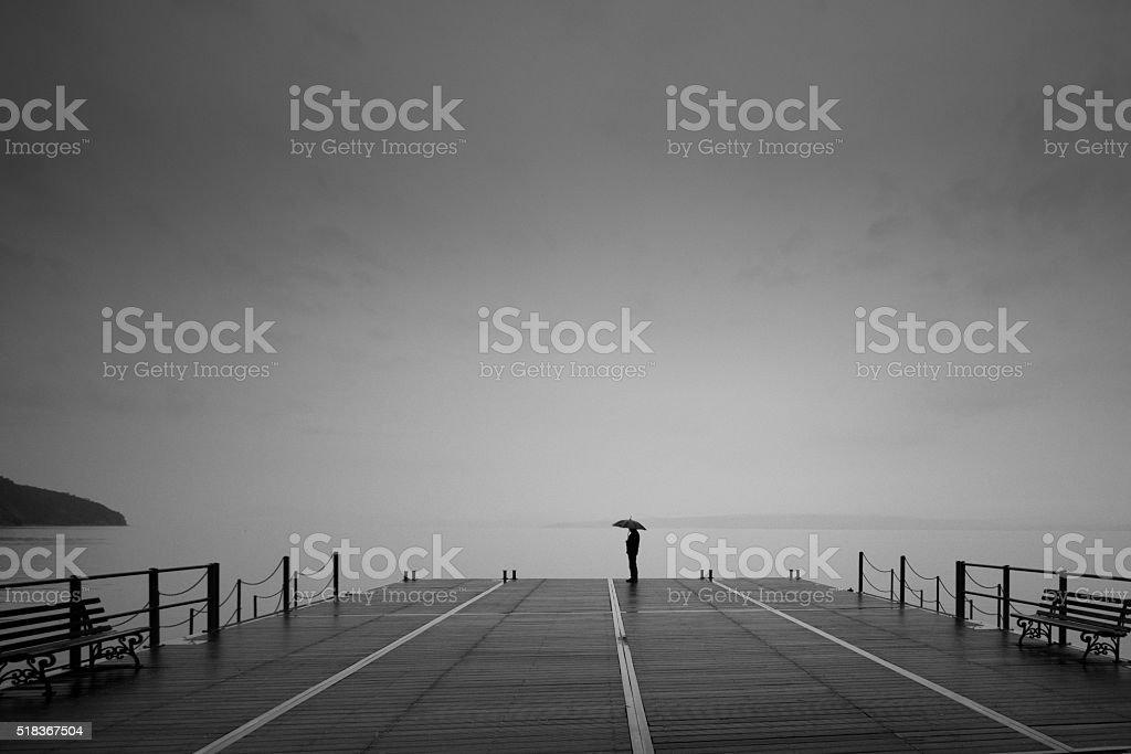 Man with black umbrella on foggy bridge stock photo