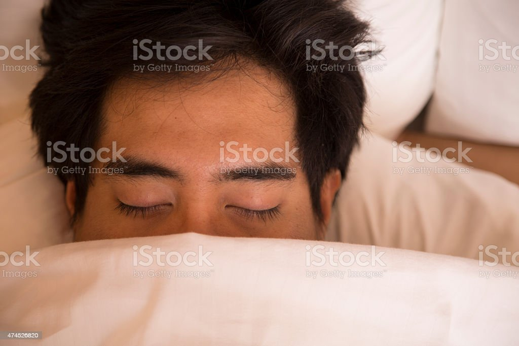 Man with blanket in comfortable hotel room bed.  Sleeping. stock photo