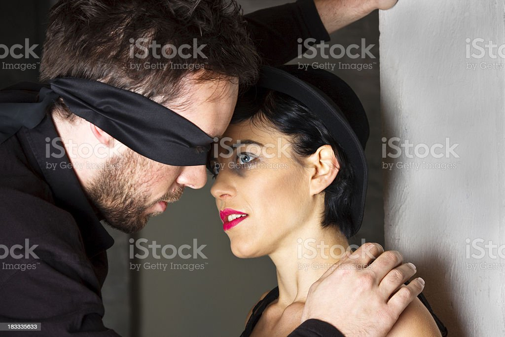 Man With Blindfold Attempting To Kiss A Woman stock photo