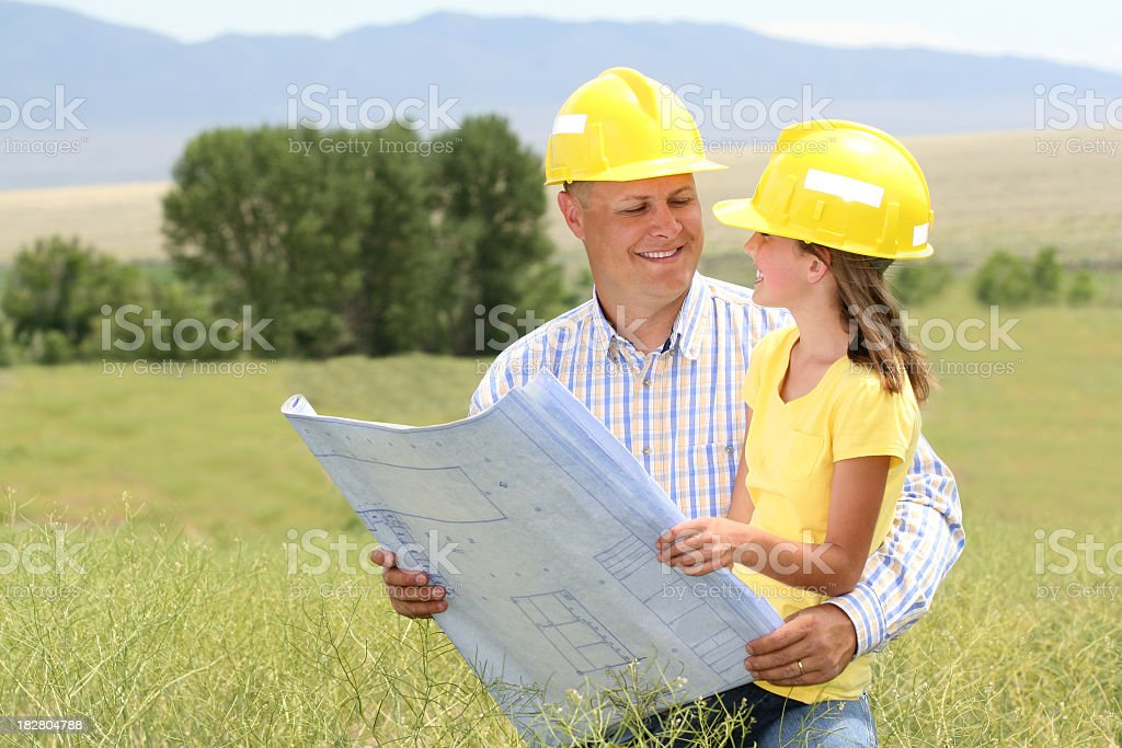 Man with blueprints in field with young girl stock photo