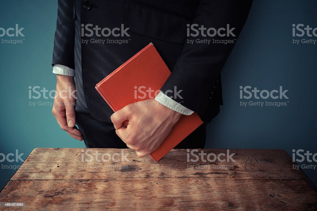 Man with book at desk stock photo