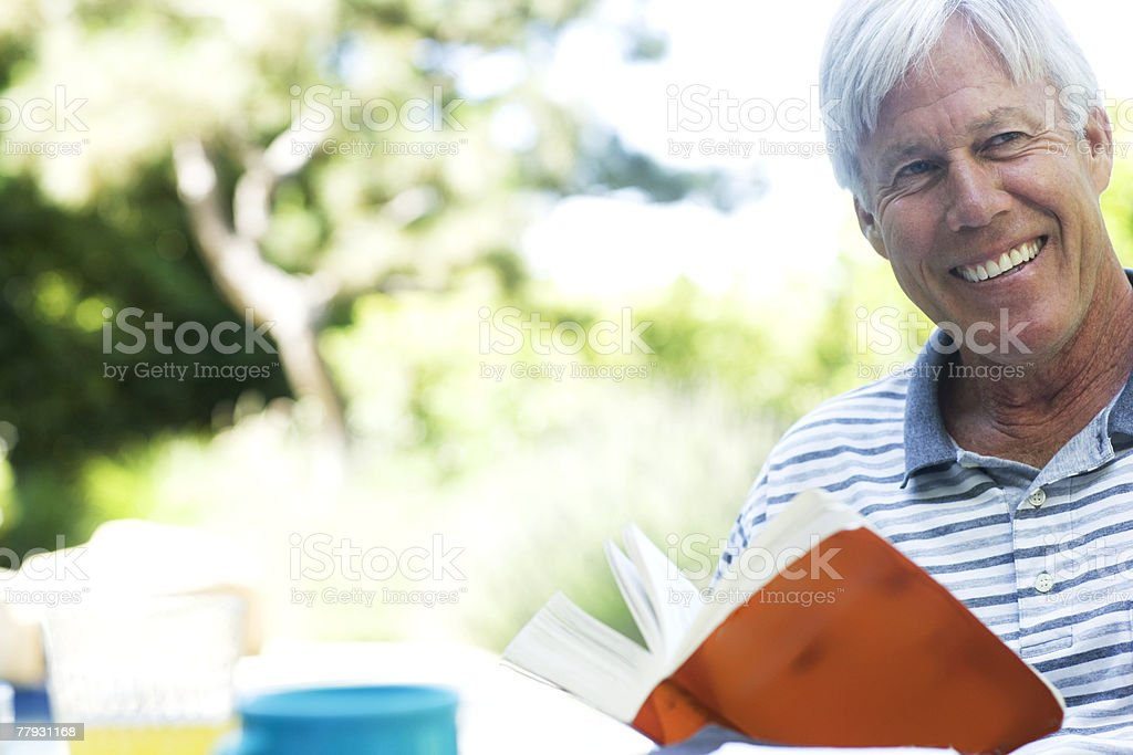 Man with book outdoors smiling royalty-free stock photo