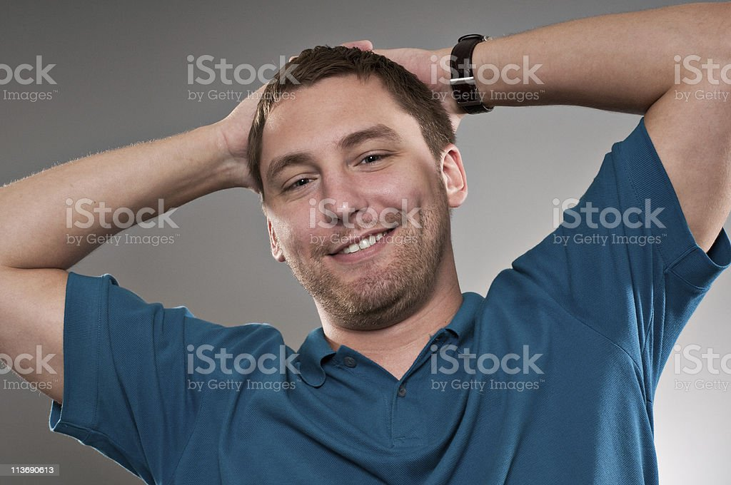 Man with both hands on head in a relaxed pose stock photo