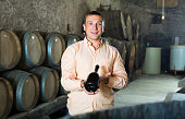 man with bottle of wine in winery cellar