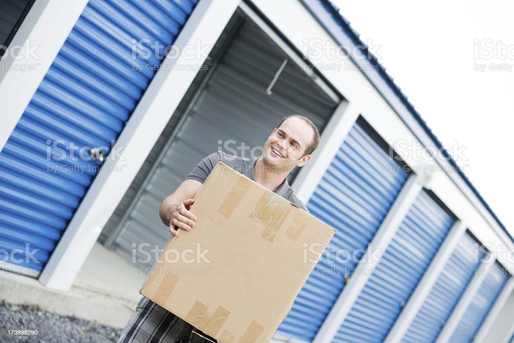 Man with Box Outside Storage Unit Lifestyle royalty-free stock photo