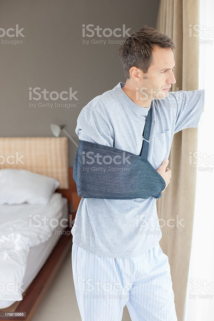 Man with broken arm looking out window stock photo
