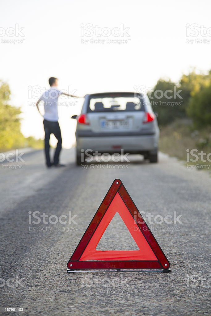 Man with broken down car on side of road using hazard sign stock photo