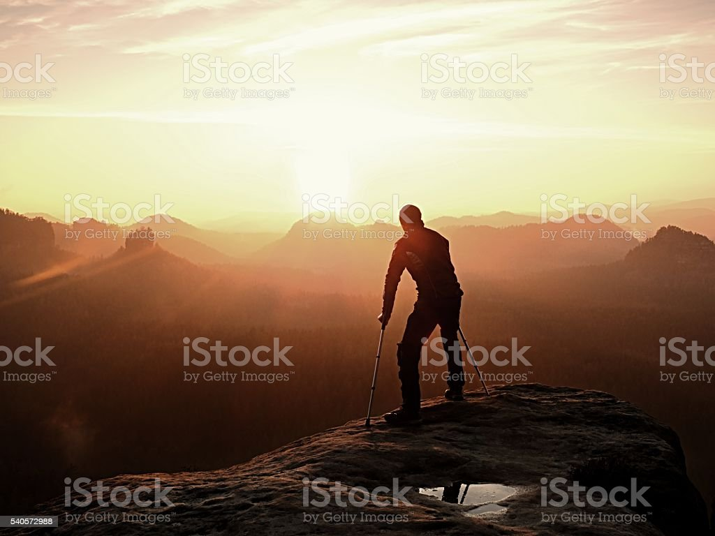 Man with broken leg and medicine crutch on mountain peak stock photo
