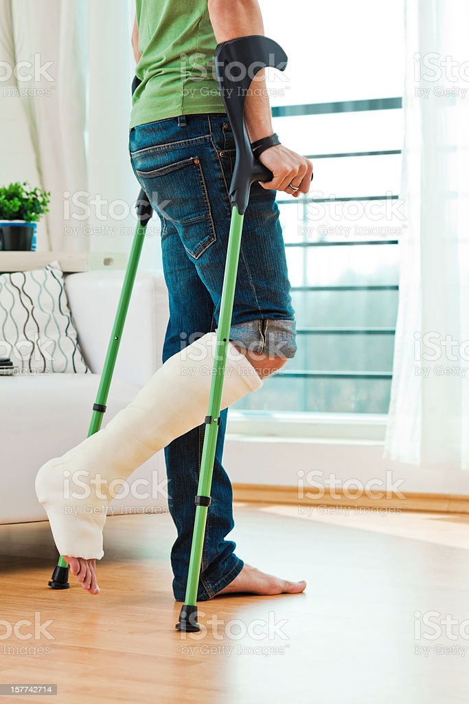 Man with broken leg at home stock photo