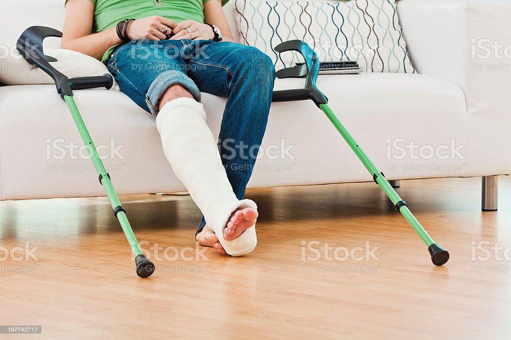 Man with broken leg at home stock photo