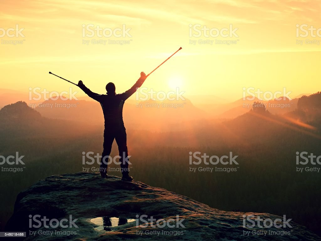 Man with broken leg  in immobilizer and medicine crutch celebrating stock photo