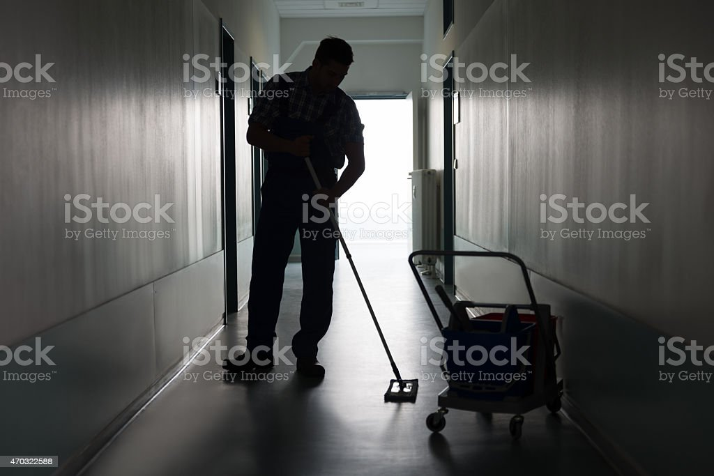 Man With Broom Cleaning Office Corridor stock photo