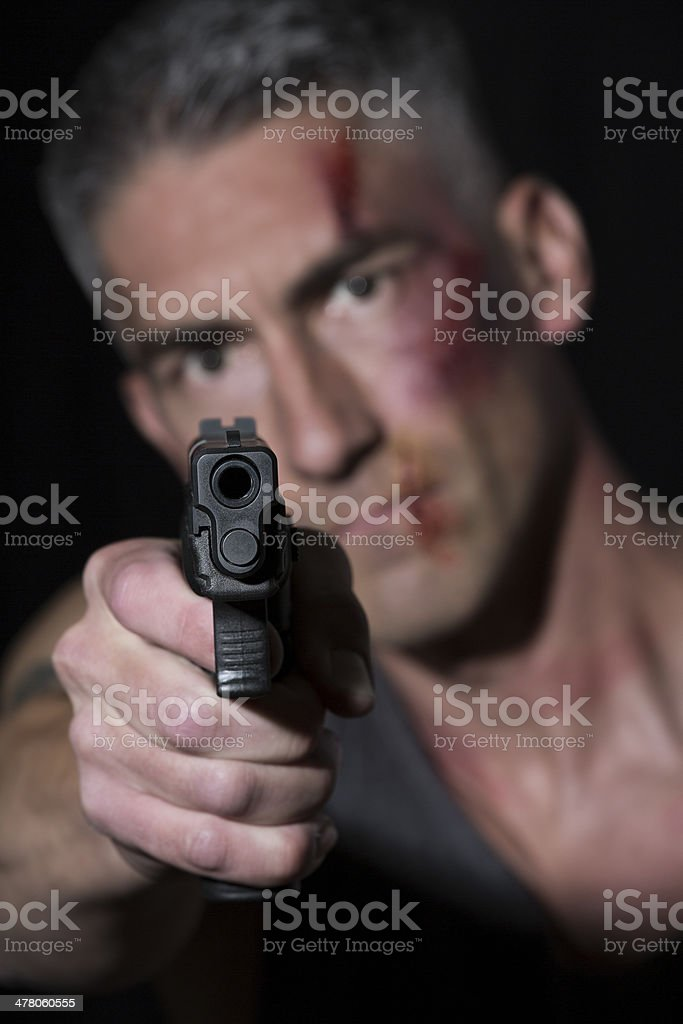 Man with bruises pointing a gun at the camera royalty-free stock photo