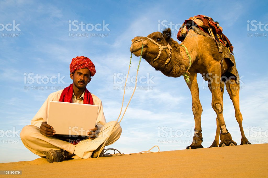 Man with Camel in Desert Using Laptop royalty-free stock photo